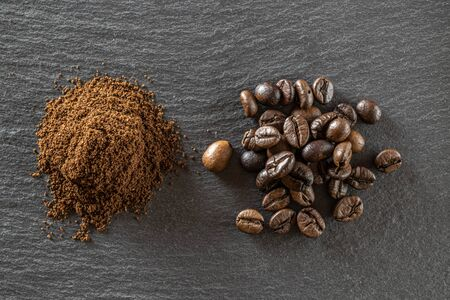 Beans for dark caffeine espresso on black food background. For cup of coffee drink in cafe. Brown roasted coffee seeds isolated for energy mocha, cappuccino ingredient. Copy space, top view 免版税图像