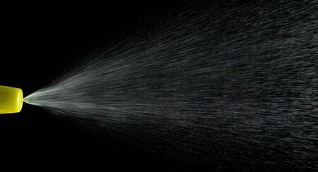 Water mist splash bottle isolated on black background. Spray liquid aerosol for perfume.