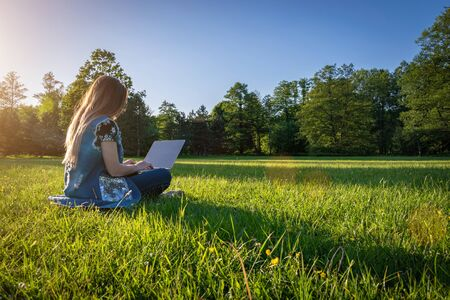 Woman online work outside. Laptop, computer business technology. Student girl working on tablet in summer nature park. People person outdoor. Escaped of office distance education concept
