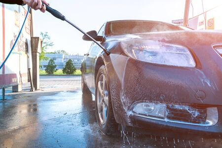Auto carwash clean station. Hand wash car with water, foam. Soap vehicle service. Care with pressure wax
