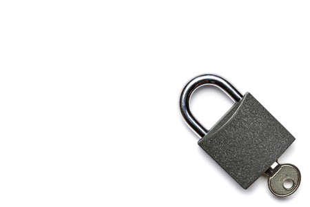 Padlock isolated on white background. Metal lock pad with key, security concept. 免版税图像