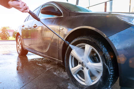Hand clean car. Auto wash from soap, foam water service, carwash vehicle. Care with pressure wax Stock Photo