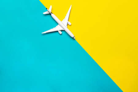 Kids playing toys. White airplane, aircraft in top view on bright blue and yellow backdrop. Flight air plane travel background with copy space for sky fly concept
