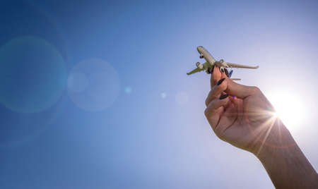 Travel background. White toy plane in girl hand flight in sunlight sky. Airplane, aircraft in bright sun light air fly concept.