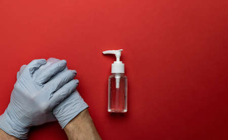 Sanitizer bottle, Medical antibacterial sanitizer gel, lab gloves - Virus protection equipment on red background. Clear sanitizer in pump bottle. COVID middle East respiratory syndrome coronavirus