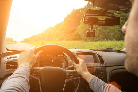 Business man driving car. Travel car trip on road at sunset. Happy young man have fun ride inside vehicle in summer sunny day. Imagens
