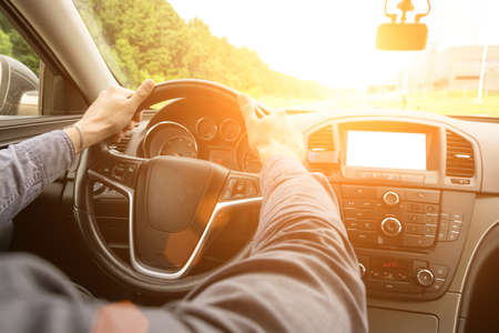 Road trip. Happy young man have fun travel inside car at sunset. Summer vacation concept with driver