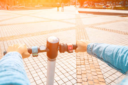 Kick scooter. Electric city bike using from girl. Urban lifestyle background. Modern and ecological transportation concept
