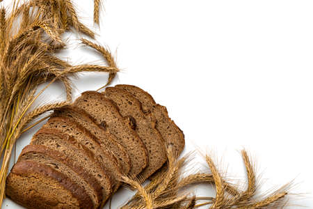 Sliced Multigrain. Rye bakery with crusty loaves and crumbs. Fresh loaf of rustic traditional bread with wheat grain ear or spike plant isolated on white background. Bio ingredients, very healthy