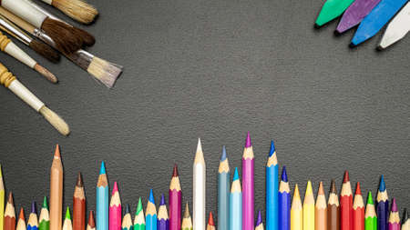 School background. School stationery with colorful pencils, chalk, brushes on black chalkboard in classroom. Design Copy Space Supplies. Top View, Flat Lay.