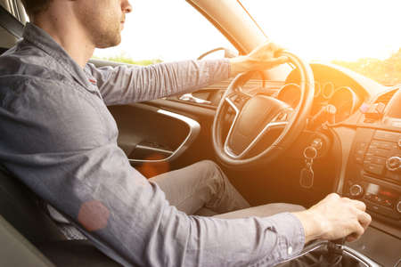Happy driver inside car at sunset. Young man have fun ride trip travel on road in summer sunny day. Drive vacation concept. Imagens