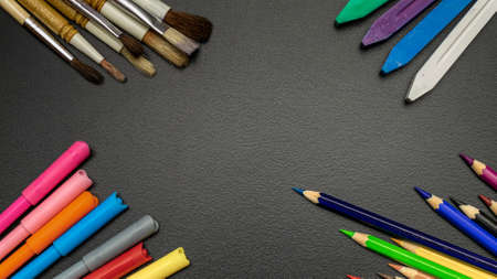 Study table. Education accessories with colorful pencils, chalk, brushes on dark school blackboard. Banner Concept Back To School.