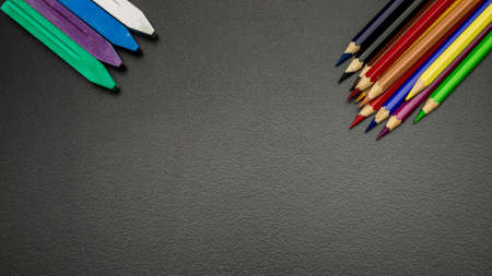 School supplies. Education accessories with colorful pencils, chalk, brushes on dark school blackboard. Concept for Teachers Day, copy space. Banque d'images