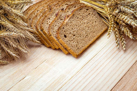Bakery products. Rye bakery with crusty loaves and crumbs. Fresh loaf of rustic traditional bread with wheat grain ear or spike plant on natural wooden background. Concept - Cooking at Home Stock fotó