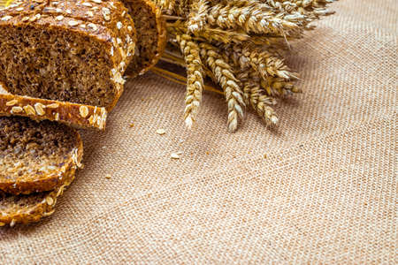 Rye bread isolated. Bakery with crusty loaves and crumbs. Fresh loaf of rustic traditional bread with wheat grain ear or spike plant on natural cotton background. Bio ingredients, healthy with seeds