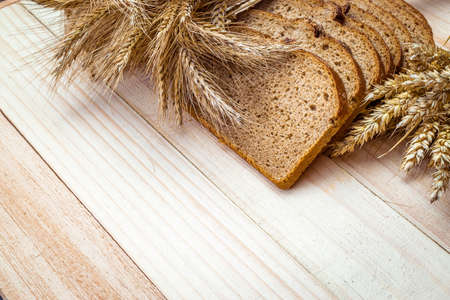 Loaf bread. Rye bakery with crusty loaves and crumbs. Fresh loaf of rustic traditional bread with wheat grain ear or spike plant on natural wooden background. Bio ingredients, very healthy seeds