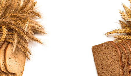 Rustic bread. Fresh loaf of rustic traditional bread with wheat grain ear or spike plant isolated on white background. Rye bakery with crusty loaves and crumbs. Concept - Cooking at Home