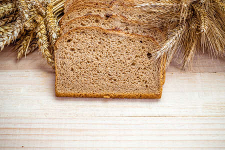 Delicious bread. Fresh loaf of rustic traditional bread with wheat grain ear or spike plant on wooden texture background. Rye bakery with crusty loaves and crumbs. Homemade baking