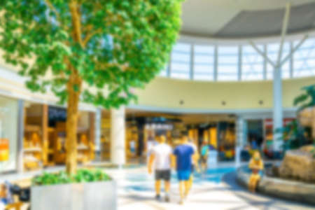 Customer store blurred background. People shopping in modern commercial mall center. Interior of retail center store in soft focus. Luxury inside business hall