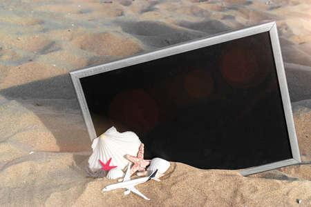 Hello summer. Starfish, seashells, toy plane and globe near blackboard on ocean nature beach. Summer vacation and product advertisement concept Stock fotó