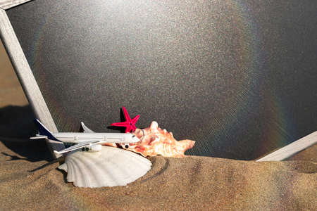 Summer concept background. Starfish, seashells, toy plane and globe near blackboard on ocean nature beach. Copy space for text