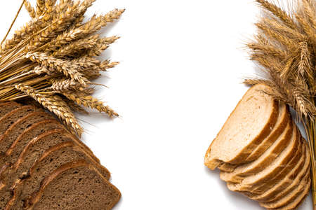 Cut bread. Fresh loaf of rustic traditional bread with wheat grain ear or spike plant isolated on white background. Rye bakery with crusty loaves and crumbs. Bio ingredients, very healthy seeds