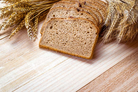 Traditional bread. Fresh loaf of rustic traditional bread with wheat grain ear or spike plant on wooden texture background. Rye bakery with crusty loaves. Design element for bakery product label Banque d'images
