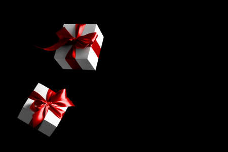 Sale background black. White gifts with red bow falling on dark background for Black Friday banner. Flying backdrop with space for text