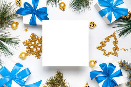 White gift box with blue ribbon, New Year balls and Christmas tree in xmas composition on white background for greeting card. Decoration and copy space for your text