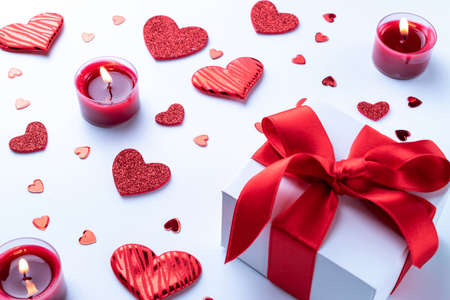 Saint Valentin background: red love hearts, romantic gift box, candle on white table. Romantic message template with copy space