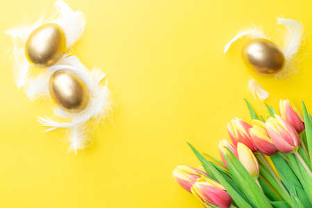 Egg color. Happy Easter decoration: golden color eggs in basket with spring tulips, white feathers on pastel yellow background. Foil minimalist egg design, modern top view template