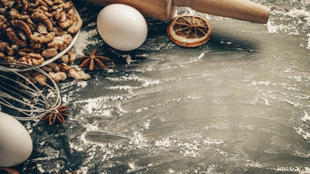 Bakery background frame. Fresh food ingredients: flour, eggs, nut and star anise, orange on black chalkboard background for bread. Still life captured from above, top view, flat lay