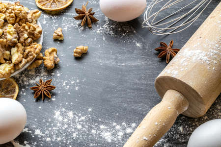 Bakery flat design. Cooking food ingredients: flour, eggs, nut and star anise, orange on dark table kitchen background for cake. Top view with copy space for text, recipe, menu