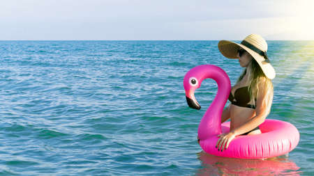 Summer hat beach. Happy young girl in bikini swimsuit, sunglasses and straw hat with pink inflatable flamingo in blue sea water on ocean background. Luxury lifestyle travel