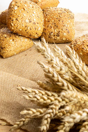 Home baked bread. Rye bakery with crusty loaves and crumbs. Fresh rustic traditional bread with wheat grain ear or spike plant on natural cotton background. Design element for bakery product label Imagens