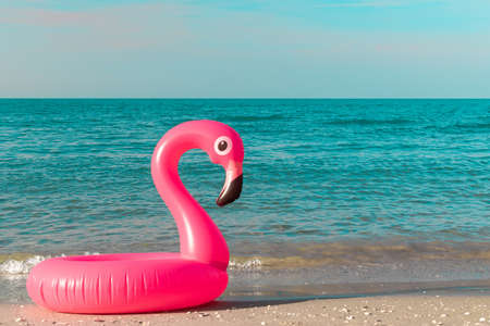Summer concept background. Pink inflatable flamingo in blue ocean water for sea summer beach background. Pool float party Foto de archivo