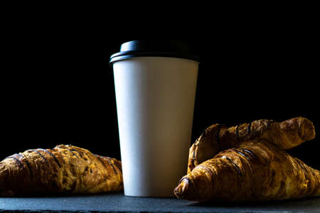 Croissant texture. French breakfast growing, fresh pastry bread with paper coffee cup in bakery on dark stone background. Bread bakery products cafe concept
