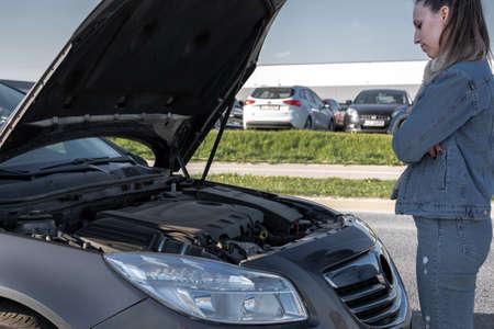 Motor car problem. Driver girl near open hood auto on road. Vehicle broken down concept