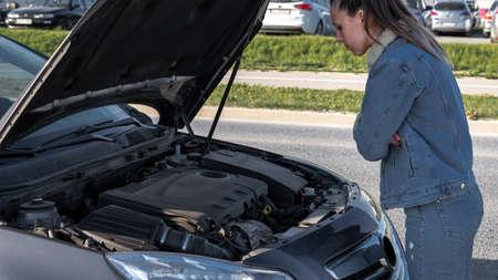 Broken down car. Vehicle engine motor problem concept. Driver girl near open hood auto