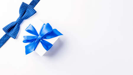 Fathers gift. White box with bow ribbon, blue bowtie or tie on light background. Concept of Fathers Day greeting card, copy space for text