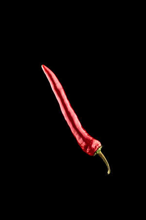 Cayenne chilli. Red hot chili paprika or spicy chile cayenne pepper isolated on black background. Fresh spice vegetable concept