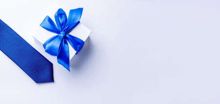 Gift dad. Blue bowtie or tie, white box with bow ribbon on light background. Happy loving family and Fathers Day concept