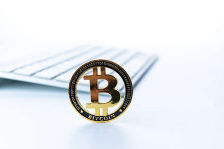 Bitcoin icon. Gold Crypto currency BTC Bitcoin with keyboard on white background. Golden Bit Coin virtual cryptocurrency or blockchain technology. Trading on the cryptocurrency exchange