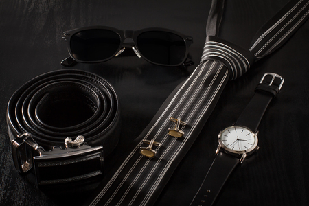 Leather belt with metal buckle, sunglasses, tie, cuff-links, watch with a leather strap on a black background