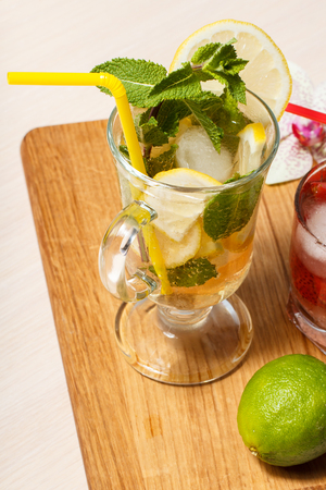 Cold refreshing summer lemonade mojito with lemon slices and mint in a tall glass and strawberry lemonade with mint in a short one on an wooden cutting board. Top view.