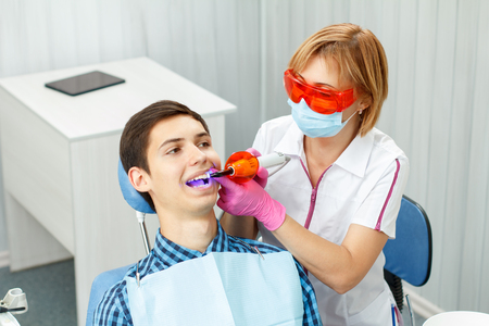 Beautiful woman dentist treating a patient teeth in dental office. Doctor wearing glasses, mask, white uniform and pink gloves. Dentistry