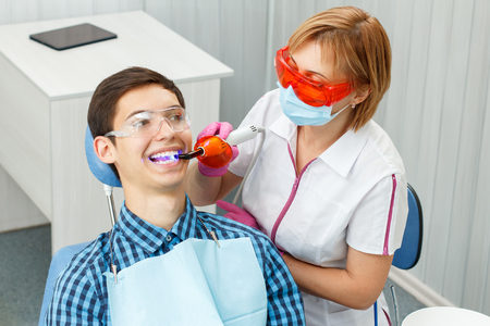 convalesce: Beautiful woman dentist treating a patient teeth in dental office. Doctor wearing glasses, mask, white uniform and pink gloves. Dentistry