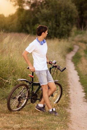 repose: Attractive young guy with road bicycle outdoors. Guy wearing white T-shirt and jeans shorts with headphones on the neck. Cycling along country trail outdoor. Riding in the countryside. Healthy active lifestyle.