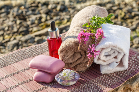Bowl with sea salt, bottles with aromatic oil, soap, wild flowers and towels with bamboo cloth on stones. Spa products on natural background