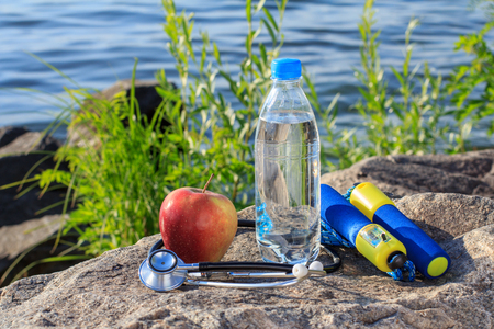 saltar: Jump rope, apple, stethoscope and bottle with water on rock with river embankment background. Summer, active lifestyle